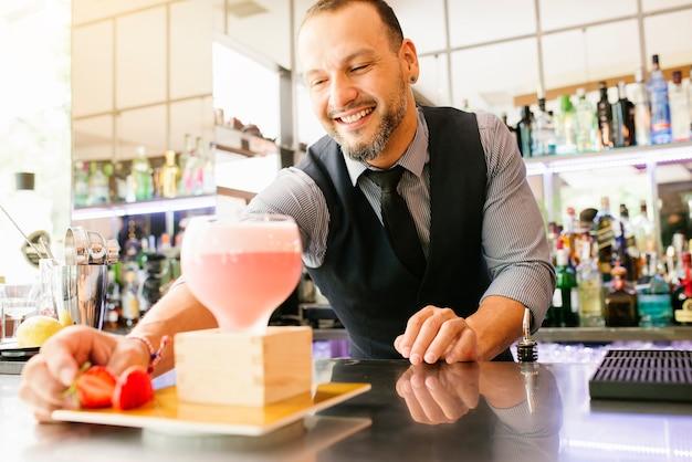 Barman experto está haciendo cócteles en el club nocturno