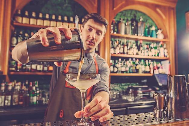Barman experto prepara cócteles en la discoteca.