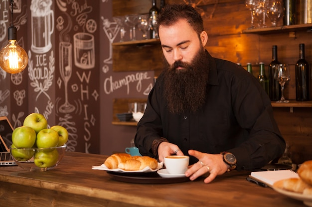 Barman guapo detrás de una barra con un café preparado. pub de época.