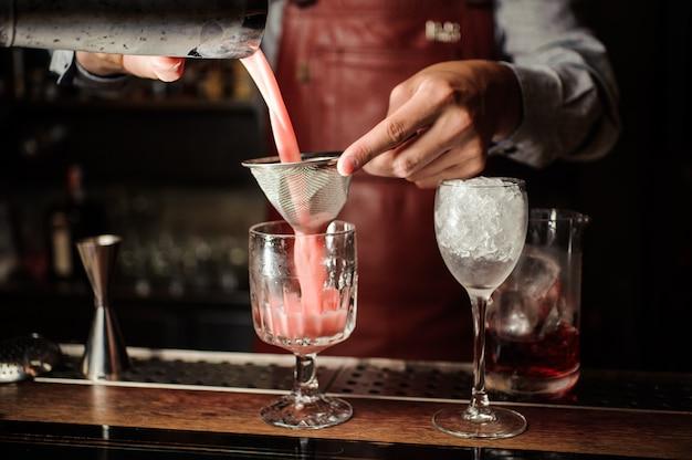 Barman está haciendo un cóctel alcohólico en el bar.