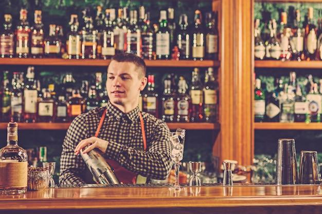 El barman haciendo un cóctel alcohólico en el mostrador del bar en el espacio del bar.