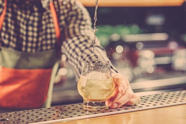 Barman haciendo un cóctel alcohólico en el mostrador del bar
