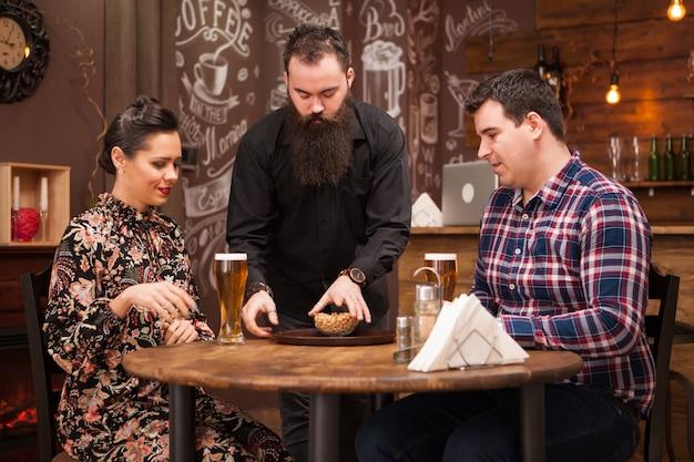 Barman hipster dando el pedido a una hermosa joven pareja. gran pub.