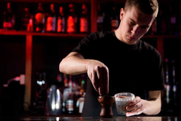 Barman llena un tazón de cerámica negro quemado para fumar narguile diferentes tipos de tabaco.