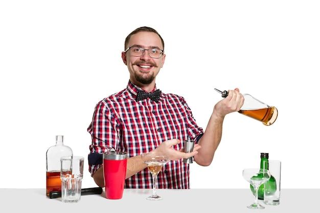 Barman masculino experto está haciendo cócteles en el estudio aislado en la pared blanca