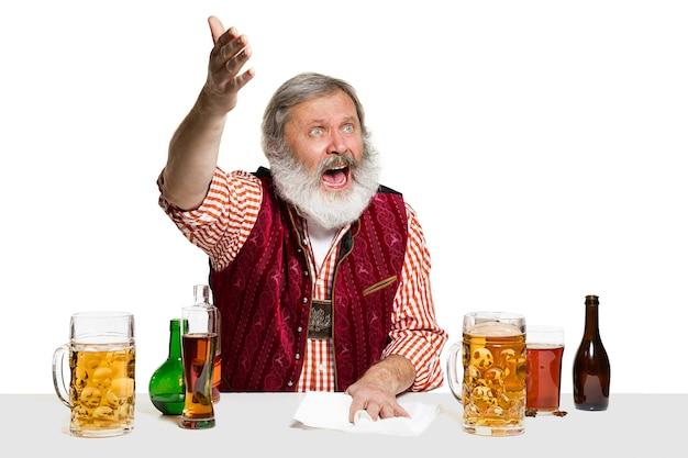 El barman masculino experto senior con cerveza en aislados en la pared blanca.