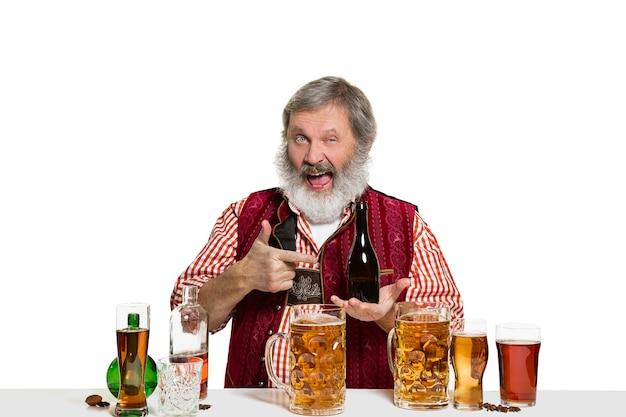 El barman masculino experto senior con cerveza en el estudio aislado en blanco