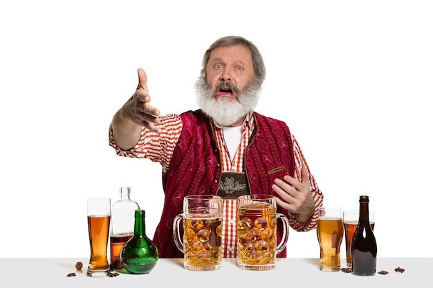 El barman masculino experto senior con cerveza en el estudio aislado en la pared blanca