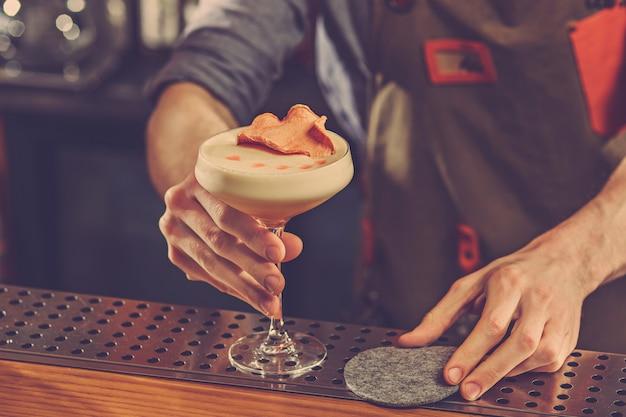 Barman ofrece un cóctel alcohólico en la barra del bar