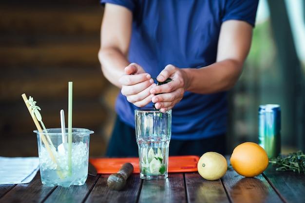 Barman prepara cóctel de alcohol de frutas a base de limón, menta, naranja, refresco y alcohol