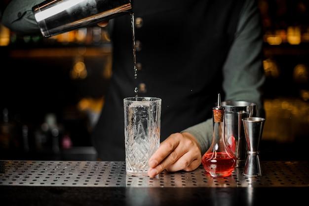 Barman preparando una bebida alcohólica fresca de la coctelera en un vaso