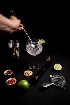 Barman preparando un cóctel de ginebra y tónica sobre un fondo negro al lado de sus ingredientes