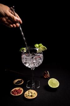 Barman preparando un cóctel de ginebra y tónica sobre un fondo negro