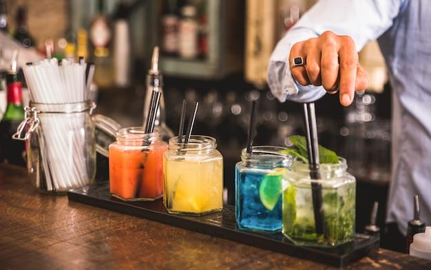 Barman profesional preparando cócteles en el bar de moda