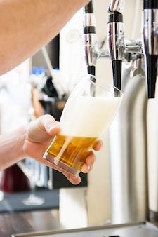 Barman que vierte la cerveza fresca en pub