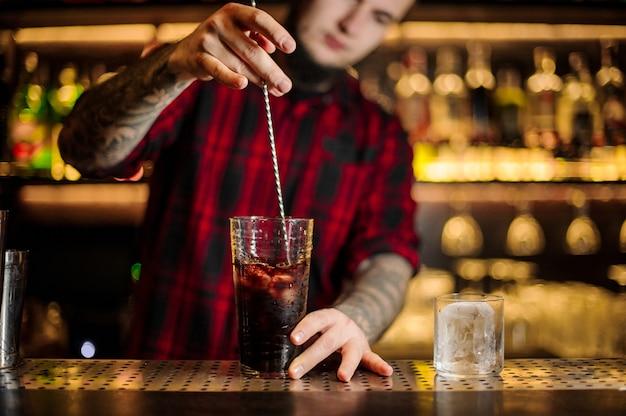 Barman revolviendo cóctel alcohólico fuerte fresco en un vaso grande en la barra del bar del restaurante