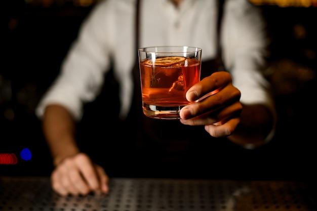 Barman sirviendo un cóctel de naranja marrón decorado con una rodaja de limón caramelizado
