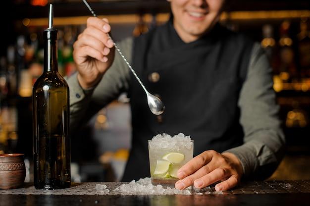 Barman sonriente revolviendo mojito fresco en una copa de cóctel