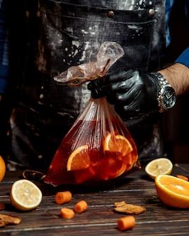 Barman sosteniendo una bolsa de cóctel con rodajas de naranja dentro