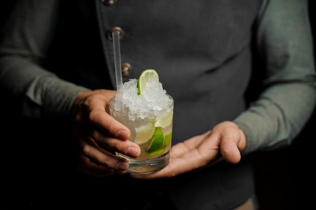 Barman sosteniendo un vaso con un mojito fresco