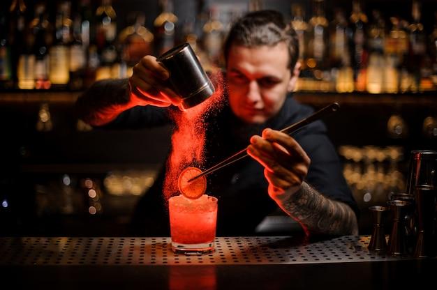 Barman tatuado agregando especias en polvo en una copa de cóctel con una rodaja de limón