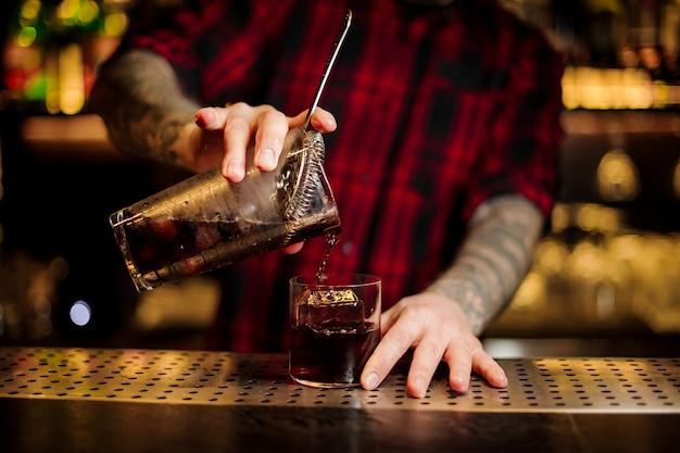 Barman con tatuajes vertiendo cóctel alcohólico fuerte fresco en un vaso en la barra contra las luces brillantes