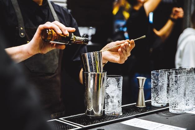 Barman en el trabajo vertiendo espíritu duro en vasos y preparando cócteles en detalle foto de alta calidad