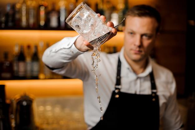 Barman vertiendo agua de un vaso con cubitos de hielo