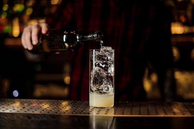 Barman vertiendo bebida alcohólica de botella en una copa de cóctel con jugo y cubitos de hielo