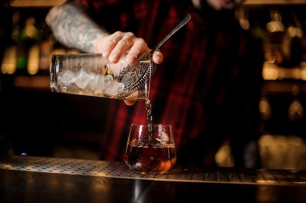 Barman vertiendo bebida fresca en un vaso de whisky dof