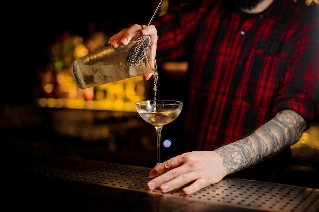 Barman vertiendo cóctel alcohólico en un vaso elegante en la barra del bar contra las luces