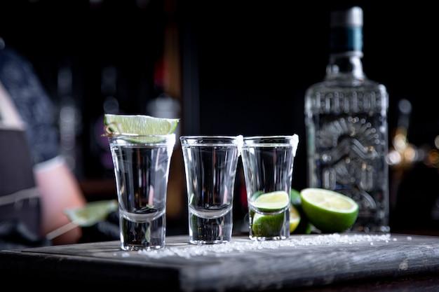 Barman vertiendo espíritu duro en vasos pequeños