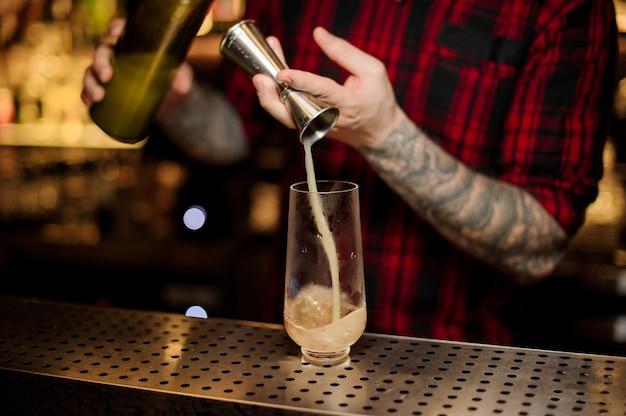Barman vertiendo una porción de bebida alcohólica con jigger en una copa de cóctel en la barra