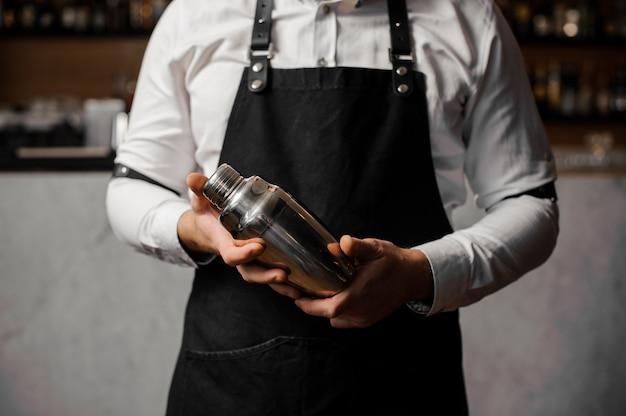 Barmans manos sosteniendo una coctelera contra la barra del bar