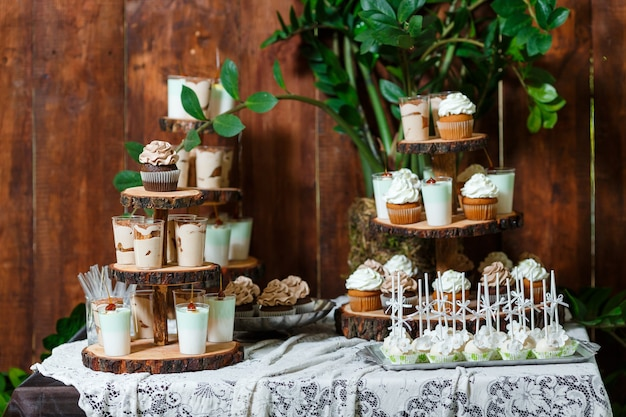 Barra de caramelo en banquete de boda de madera con una gran cantidad de diferentes dulces cupcakes soufflé y tortas