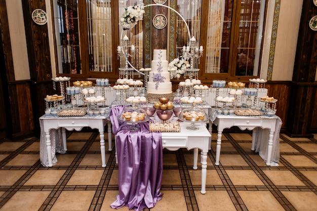 Barra de caramelo de boda pomposa y decorada con pastel de bodas de lavanda