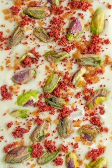 Barra de chocolate blanco artesanal con pistachos y frambuesas secas sobre fondo brillante. vista superior.