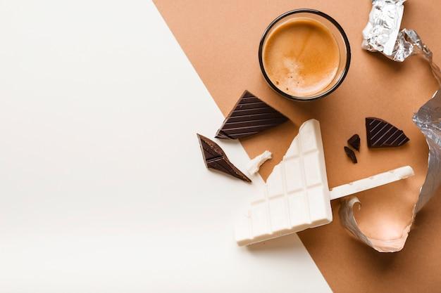 Barra de chocolate blanco y oscuro con vaso de café sobre fondo dual