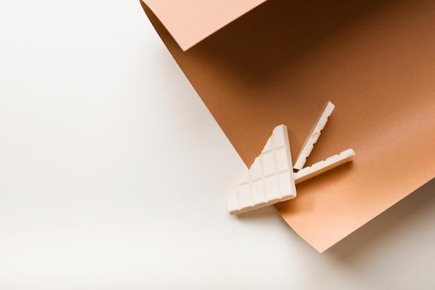 Barra de chocolate blanco en el papel marrón de la tarjeta sobre el fondo blanco