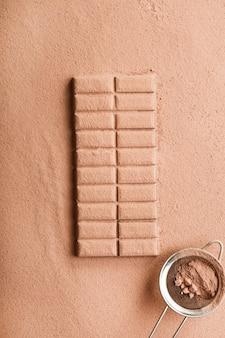 Barra de chocolate espolvoreada con cacao en polvo con tamiz.