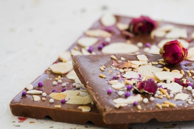 Barra de chocolate con frutas secas y rosa sobre fondo blanco