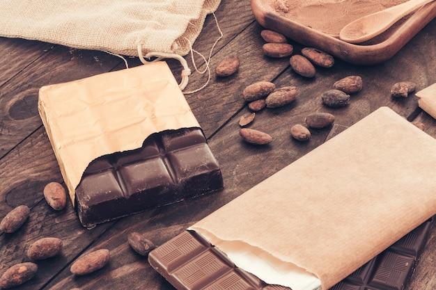 Barra de chocolate con granos de cacao en la mesa de madera