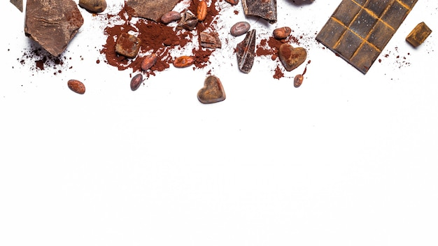 Barra de chocolate, granos de cacao, pedazos en un fondo aislado blanco.