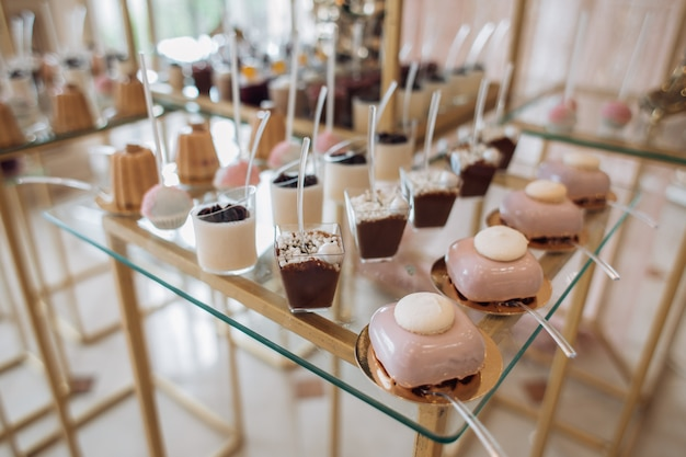 En la barra de chocolate hay moldes con porciones de postres y galletas cubiertas de crema rosa.