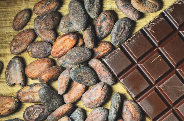 Barra de chocolate negro orgánico y granos de cacao en madera natural