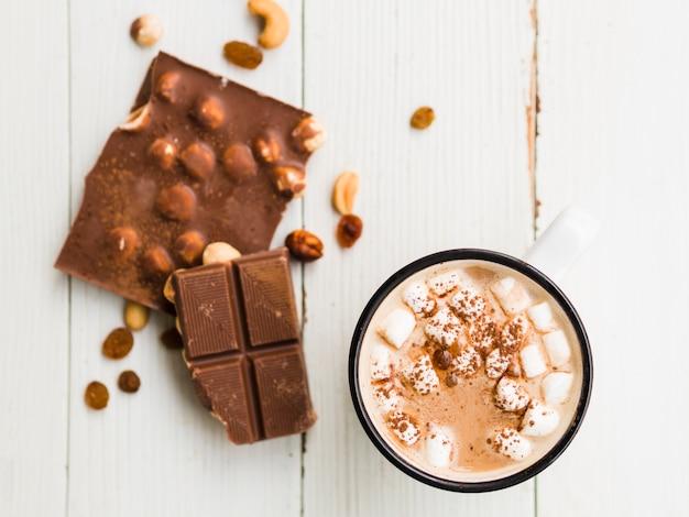Barra de chocolate con nueces y taza de cacao con malvaviscos.