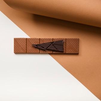 Barra de chocolate oscuro y marrón en el papel de la tarjeta contra el fondo blanco