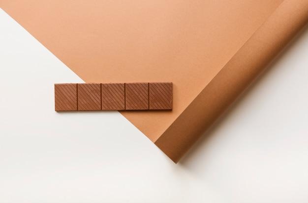 Barra de chocolate en papel enrollado sobre fondo blanco