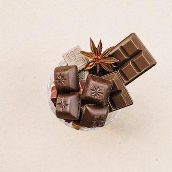 Barra de chocolate y piezas en vidrio sobre fondo beige