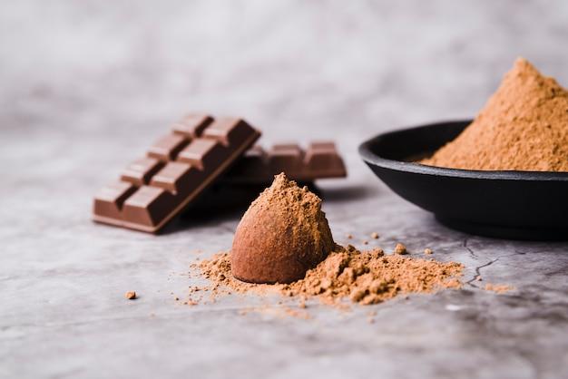 Barra de chocolate y polvo de cacao cubierto de trufa en el fondo de hormigón